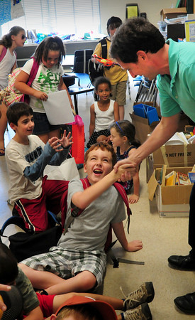Newburyport: Teacher John Gangemi shakes his students' hands, here Cole Brown, 9, as they ready to leave the Bresnahan School yesterday as Newburyport Schools let out for the season. Bryan Eaton/Staff Photo