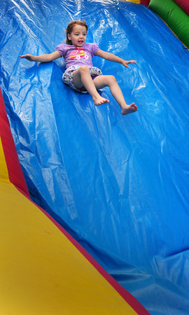 Amesbury: Katreina Green, 3, slides down on the inflatable obstacle course at the Kid's Kingdom at Amesbury Town Park. The ride was sponsored by Market Square Baptist and First United Methodist Churches for Kids' Day in the Park, part of Amesbury Days. Bryan Eaton/Staff Photo