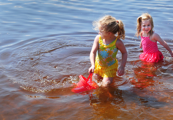 Amesbury: Sisters Casey Metcalf, 5, left, and Marley, 3, collect water for the moat of their sand castle they were building. They were at a very crowded Lake Gardner Beach yesterday afternoon. Bryan Eaton/Staff Photo