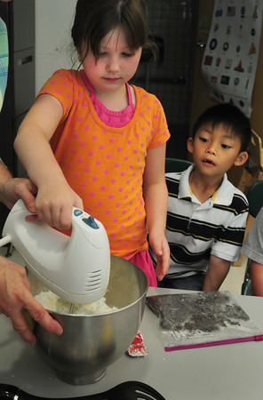 Salisbury: Karissa True, 6, mixes together indredients to make Heavenly Dirt, with the main ingredient being Oreo cookies as Johnny Nguyen, 6, waits his turn. The two were in a cooking class at the summer program at Salisbury Elementary School yesterday. Bryan Eaton/Staff Photo