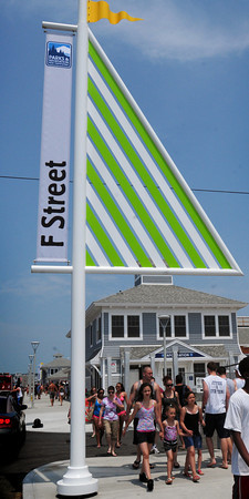 Hampton: Strollers walk past the new information booth at Hampton Beach, also containing one of the new bath houses constructed. New signs with a nautical theme mark side streets off Ocean Boulevard. Bryan Eaton/Staff Photo