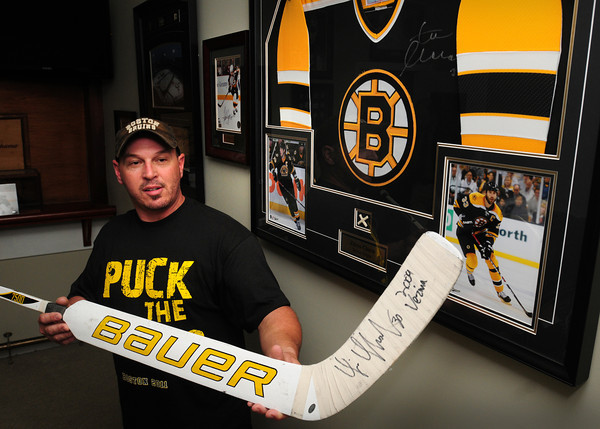 Newburyport: Boston Bruins super-fan and collector Steve Jewett of Plum Island holds the most prized piece of his collection, a stick used and signed by goalie Tim Thomas. Jewett, co-owner of the Thirsty Whale usually catches games at home or at the game, but will be at his pub tonight with friends and customers. Bryan Eaton/Staff Photo