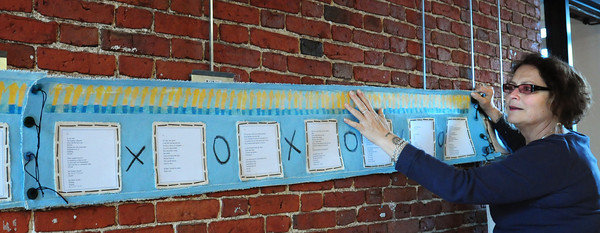 "Newburyport: Artist Paula Estey hangs ""My Daily Bread"" a poem scroll at the entrance to her art show at the Coombs Gallery at the Newburyport Art Association. Bryan Eaton/Staff Photo"