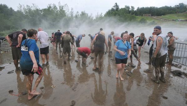 Amesbury: Runners wash the mug off themselves during Saturday's Worrior Dash at Amesbury Sports Park . Jim Vaiknoras/Staff photo