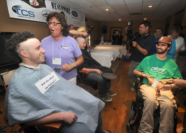 Amesbury: Nate Bibaud looks on as his former roommate Kieran Egan gets a Mohawk from barber Esther Sayer at the Clip it and Rip it fundraiser at Amesbury Sports Park Friday night. Jim Vaiknoras/Staff photo