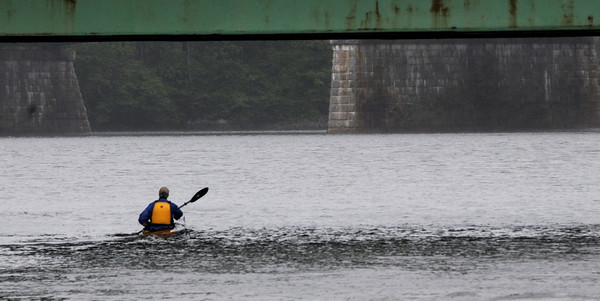 Amesbury: A kayaker makes his way up the Merrimack River under a section of the under repair Hines Bridge in the rain Sunday morning. Jim Vaiknoras/Staff photo