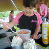 Danvers: Wylinn Palmisano, 6, of Goodies Ice Cream add sprinkles during the Ice Cream Scoop-ah-Bowl at the Danvers Family Festival at Endicott Park Saturday. JIm Vaiknoras/Staff photo