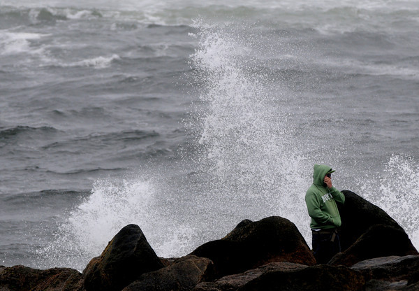 Newbury: A man makes call on his cell phone as waves pound the rocks near the central parking lot on Plum Island. Jim Vaiknoras/Staff photo