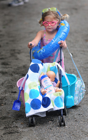 Danvers:Asa Labell, 2, of Hamilton pushes her baby and some sun screen in the Doll Carriage Parade at the Danvers Family Festival at Endicott Park Saturday. JIm Vaiknoras/Staff photo