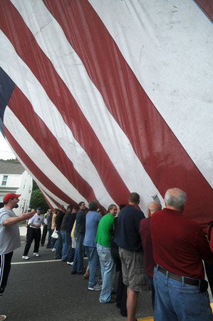Amesbury: About 40 people help roll up the 30x58 foot Patriot Flag on School Street infront of the Amesbury Fire Station Saturday afternoon. The flag which suspended from 2 ladder trucks, paid tribute to the first responders, the victims and  families of the Sept 11 terrorist attack as well as those in the military. Jim Vaiknoras/Staff photo