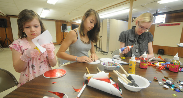 """Amesbury: Linda Bullis, 6, Caroline Conte, 13, and Zanthia Dwight, 14,work of """"Heavenly Faces""""  at a workshop by Amesbury artist Gay Cox  at All Saints' Anglican Church. Jim Vaiknoras/Staff photo"""