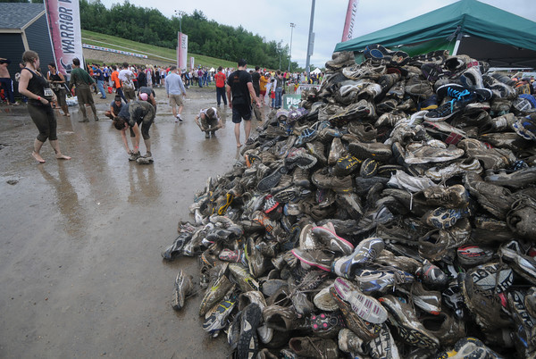 Amesbury:A pile of mud covered sneakers stand testiment to those runners who ran in Saturday's Warrior Dash at Amesbury Sports Park . Jim Vaiknoras/Staff photo