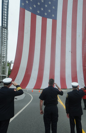 Amesbury: Members of teh Amesbury Fire Dept salute the 30x58 foot Patriot Flag on School Street infront of the Amesbury Fire Station Saturday afternoon. The flag which suspended from 2 ladder trucks, paid tribute to the first responders, the victims and  families of the Sept 11 terrorist attack as well as those in the military. Jim Vaiknoras/Staff photo
