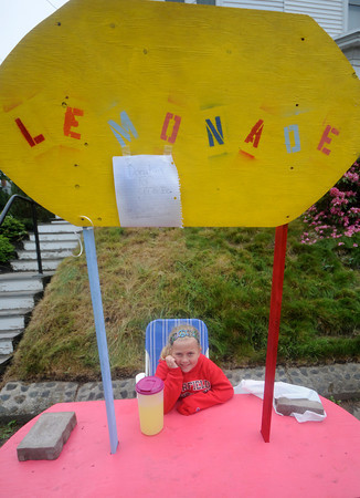 NEWBURYPORT: Lydia Hanson, 7, sits at a lemonade stand on State Street  Sunday. She put up the stand, built by her dad, to raise money for Girls Inc.<br /> Lydia chose her grandparents house on State Street to take advantage of the Garden Tour stop.  Due to teh cold weather she was also selling hot cider. Jim Vaiknoras/Staff photo