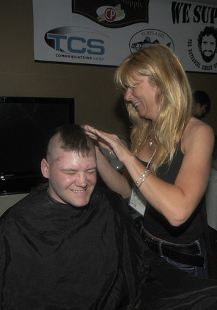 Amesbury: Charlie Lagassi cringes as April MacFarland of Backstage in Peabody removes his hair at the Clip it and Rip it fundraiser at Amesbury Sports Park Friday night. Jim Vaiknoras/Staff photo