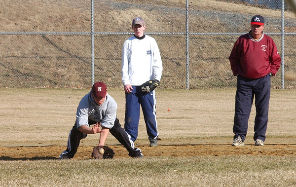 Newburyport: <br /> Coach Bill Pettengell watches as Keith Carter catches a ball during the first day of spring practice yesterday in Newburyport.<br /> Photo by Bryan Eaton/Newburyport Daily News. Monday, March 15, 2004