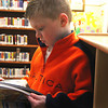 Amesbury: Seth Hagan, 6, of Amesbury, flips through the pages of a book in the childrens section of the Amesbury Public Library Wednesday afternoon as he and his brother Grady look for something fun to read. Photo by Ben Laing/Staff Photo