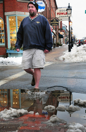 Newburyport: Yesterday's rain and warmer temperatures melted some of the snow into puddles. Dan Kenney of Salisbury, who says he wears shorts often when the weather warms, crosses a puddle at Middle Street in downtown Newburyport. Sun and warmer temperatures should increase the snow melt today and tomorrow. Bryan Eaton/Staff Photo