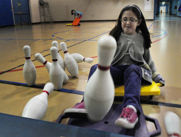 """Rowley: Sara Winnick, 8, smashes into some plastic bowling pins at the Pine Grove School in Rowley on Thursday morning. The students were playing """"human bowling"""" one of the more popular activities in gym class. Bryan Eaton/Staff Photo"""