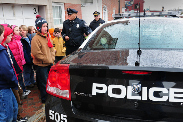 Newburyport: Newburyport police officer Keith Carter shows off a cruiser to students, along with Amesbury Sgt. William Scholtz at the Newburyport Police Station on Thursday. The two gave a talk to the children at the Inn Street Montessori School where they answered many questions afterward. Bryan Eaton/Staff Photo