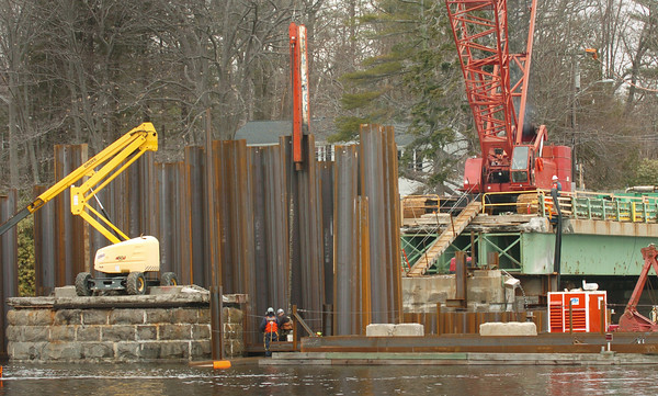 Amesbury: A jack pounds in corrugated metal which will enclose an abutment of the Hines Bridge in a view taken from Deer Island. Bryan Eaton/Staff Photo