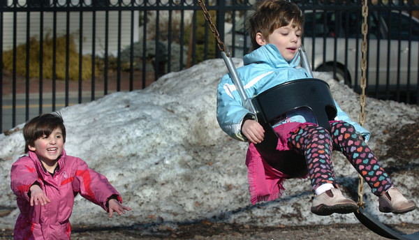 Newburyport: Morgan Trout, 4, pushes her twin sister, Sydney, during yesterday afternoon's sunny weather. The two, from Newburyport, were at the Kelley School Playground with their mother Laurie. Bryan Eaton/Staff Photo