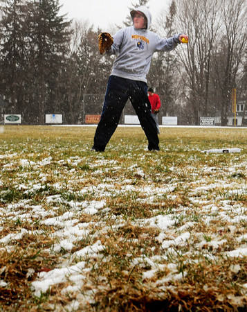 Newburyport: Newburyport High baseball captain Ryan O'Connor throws the ball on the first day of practice and first full day of spring as snow accumulated on the Lower Field yesterday afternoon. Bryan Eaton/Staff Photo