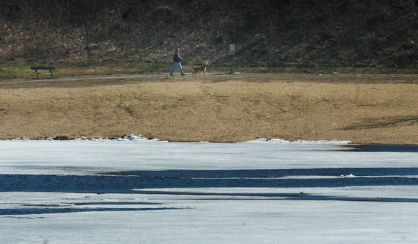 Amesbury: The ice is finally melting on Lake Gardner, but there are no sunbathers yet, just a man walking his dog along the beach yesterday morning. Bryan Eaton/Staff Photo
