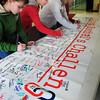 Newburyport: Students sign the Rachel's Challenge mural after a presentation. From left, Krysta Padellaro, Gabby Balkind, Kate Costello, all 10, and Adam Raymond, 11. Bryan Eaton/Staff Photo