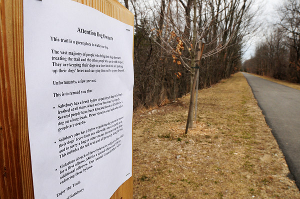 Salisbury: A sign on the Salisbury section of the rail trail asks people to clean up after their dogs and to keep them leashed. Bryan Eaton/Staff Photo