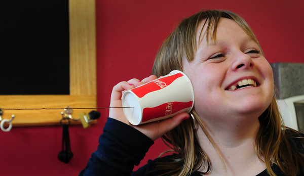 Newburyport: Courtney Lehan, 12, laughs as she listens to counselor Jared Ingersoll on a telephone made of string and plastic cups Monday afternoon. They were in the craft room at the Kelley School Drop-In Center in Newburyport. Bryan Eaton/Staff Photo