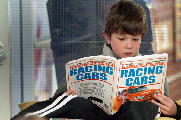 Amesbury: Calvin Heline, 7, reads a book on racing at Amesbury Elementary School on Tuesday during library time for his class. When asked what kind of books he likes best, he answered most kinds. Bryan Eaton/Staff Photo