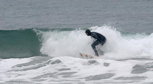 salisbury: A surfer take advantage of the warm weather Sunday to catch a wave off Salisbury Beach. JIm Vaiknoras/Staff photo