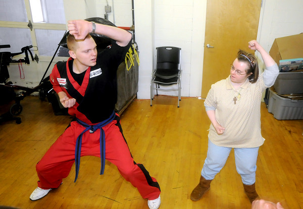 Amesbury: Chris Daigle, who is an instructor at Ocasio's Martial Arts in Plaistow, N.H works with Lianna F. at Coastal Connections in Amesbury, Lianna was one of about 15 people to earn their white belts in karate. Jim Vaiknoras/Staff photo