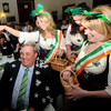 Newburyport: Provident Bank workers Tracey Jackson, Kim Chatigny and Rachel Ela cover Newburyport Bank President Richie Eaton with flowers during a song celebrating his retirement at the 9th St Patrick's Day Luncheon at the Masonic Temple in Newburyport. JIm Vaiknoras/Staff photo