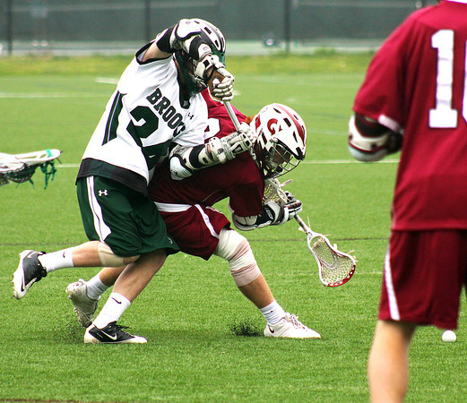 Byfield: JC Vivian (20) of Governors Academy fends off a check by a member of Brooks' lacrosse team during Monday afternoon's game in Byfield. Photo by Ben Laing/Staff Photo