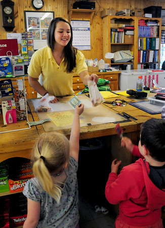 Amesbury: Mimi Auger of Merrimac hands penny candy to cousins Evie Estabrook, left, of Bradford, and Cillian Hardy, both 4, of Amesbury at Eastern Lumber and General Store. Bryan Eaton/Staff Photo