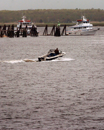 Salisbury: This motorboat has no trouble travelling up the Merrimack River near the mouth yesterday at low tide in a view from Salisbury Beach State Reservation. But larger vessels, as the party boats in rear, are having a harder time as a sandbar has increased in size forcing boats to maneuver around it. Bryan Eaton/Staff Photo