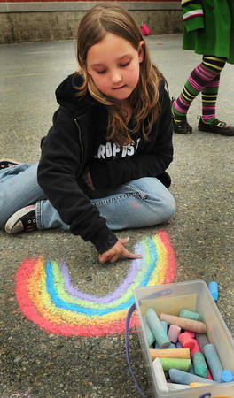 """Salisbury: Madisyn Weldon, 8, draws a rainbow during recess at Salisbury Elementary School yesterday afternoon before the rain started spitting. She likes colorful artworks and said she's """"literally drawn 100 pictures for my mother."""" Bryan Eaton/Staff Photo"""