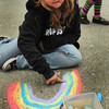 "Salisbury: Madisyn Weldon, 8, draws a rainbow during recess at Salisbury Elementary School yesterday afternoon before the rain started spitting. She likes colorful artworks and said she's ""literally drawn 100 pictures for my mother."" Bryan Eaton/Staff Photo"