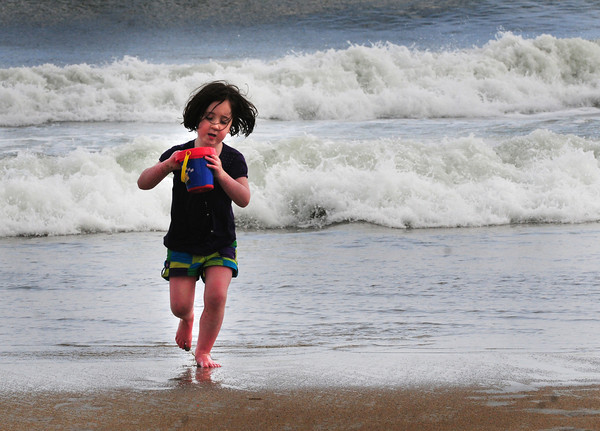 Salisbury: Kaylyn Burke, 5, comes out of the ocean at Salisbury Beach with a bucket of water for the sand castle she was building yesterday afternoon in the 80 degree temperature. The youngster, from Tewksbury, was there with her brother,  Joey, 5, and her Nana, Mary Jean Murphy. Bryan Eaton/Staff Photo