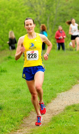 Newburyport: Brett Ely of Natick is the first woman across the finish line, her husband, Matt, won the race. Bryan Eaton/Staff Photo
