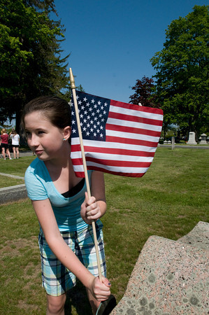 Newburyport: Nock Middle School students, including Emily Phelan, 12, planted new flags on the graves of veterans at the Belleville and St. Mary's Cemetery's yesterday morning to ready them for Memorial Day. Bryan Eaton/Staff Photo