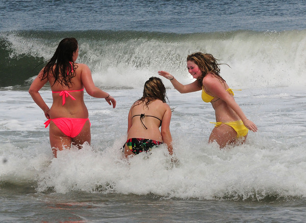 Salisbury: These Haverhill women, on summer break from their respective colleges, got a headstart to the season as they hit the waves at Salisbury Beach yesterday afternoon. From left, Amanda Cahill, Lexi Libby and Tamara Jardine. Bryan Eaton/Staff Photo