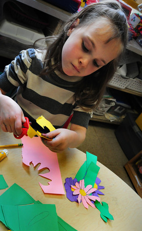 Amesbury: Charlotte Rinaldi, 6, cuts flowers out of colored paper in Sharon Nash's kindergarten class at Amesbury Elementary School on Monday morning. The students are creating a mural of a class garden with the flowers, bees, rabbits, etc. Bryan Eaton/Staff Photo