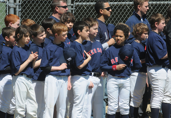 Beverly:Player and coaches for the Major League Red Sox cover their hearts during the National Anthem the Opening Day ceremonies for the Beverly Little League at Harry Ball Field Sunday morning. The boy play for the farm team the Rock Hounds. Jim Vaiknoras/Staff photo