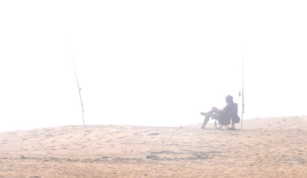 Newbury: A surf caster waits for a bite in heavy fog Friday morning on teh Beach on Plum Island. Jim Vaiknoras/Staff photo