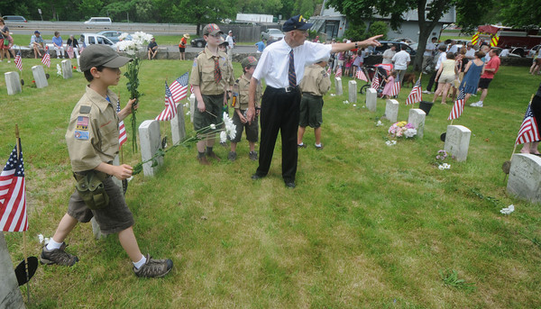 Newburyport: Ralph Ayers directs scouts as they place carnations on the graves of veterans at Veteran's Cemetary in Newburyport at the close of the Memorial Day service Monday. Jim Vaiknoras/Staff photo