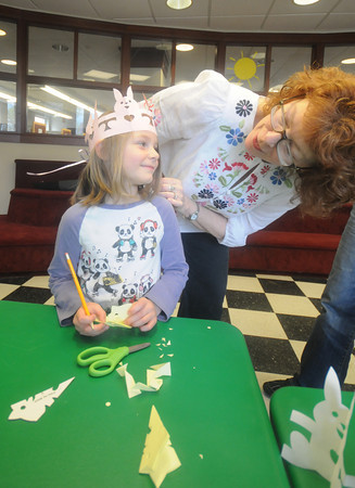 newburyport: Chloe Stuart , 5, of Kinston NH, talks with author Judith Moffatt as she makes cat snowflakes at the Newburyport Library during the Newburyport Literarry Featival. Jim Vaiknoras/Staff photo