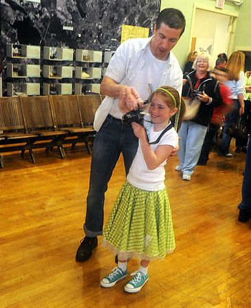 """Amesbury: Anna Penny , 9, of Amesbury , takes some photos of her friends at a pre father daughter dance  promenade at Amesbury city hall Friday night. Over 100 girls and their dads later attended """" A 1950's Sock Hop"""" at the Cashman School/ Jim Vaiknoras/Staff photo"""